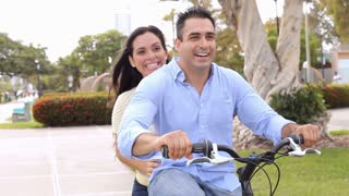 Young Hispanic Couple Riding Bike In Park