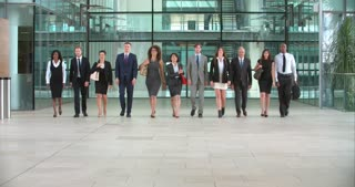 Business colleagues walking towards camera in a modern foyer