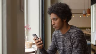 Young Man Using Mobile Phone To Update Social Media In Cafe