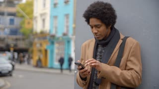 Young Man Using Phone On Busy City Street