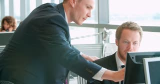 Manager talking with two colleagues in busy open plan office