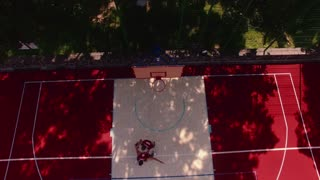 Aerial. Guys play basketball on the red playing field