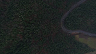 Aerial view of a curved winding road betwen big mountains 4k 60fps