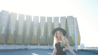 Beautiful fashion girl in black dress posing and smiling at camera on urban architecture background.