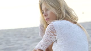 Beautiful girl close-up shooting. looks at the sea and the camera. shooted in golden hour. emotional face on the beach. Close Up. Slow Motion.