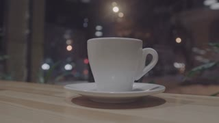 Cup of coffee in cafe. with blurry background(and bokeh) at night time. Timelapse