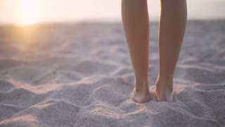 feet close-up. The girl goes to the sea at sunset. Slow motion. close-up. beautiful slim body