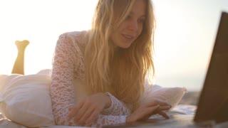 Girl using laptop at the beach 4k.