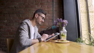 happy cute male college student using tablet computer. guy sitting in a cafe with a tablet in her hands
