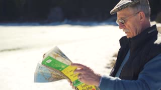 Old Man looking at map with lake and mountains on background