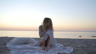 The girl lies on the beach between the pillows and blankets. sunset, romance, slow - motion, close - up. beautiful slim body