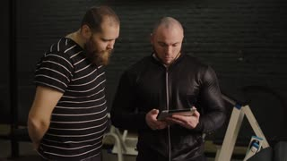 trainer with tablet in hands work with fat man in the gym