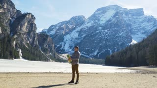 Young Man looking at map with lake and mountains on background