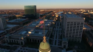Orbiting Indianapolis State Capitol And Flag At Sunrise