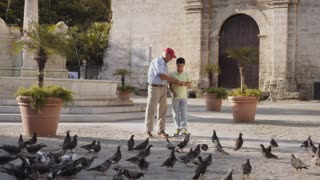 1-Grandpa And Grandson Feeding Pigeons With Bread On Vacations