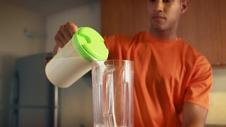 1 Man Athlete Prepares Protein Milk Shake At Home