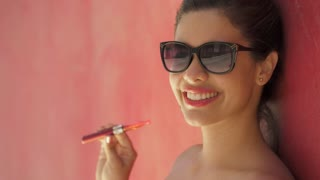 12-Slowmotion Girl Smokes Electronic Cigarette E-Cig Against Red Background