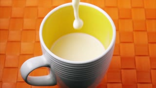 16 Milk Dropping In White Cup On Orange Table