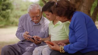 17-Boy Helping Grandpa Surfing Internet On Mobile Phone