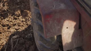 24-Tractor Moving In Field Closeup Of Tire And Ground