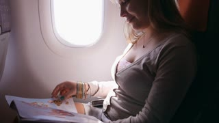 2of2 People, traveler, happy woman traveling on plane, reading magazine