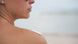 9-Young Woman Smearing Shoulders With Sun Cream At Beach