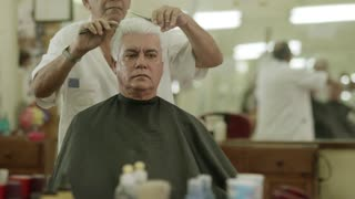 Active retired old people, man getting an haircut by senior barber in old fashion barber's shop or male beauty parlor