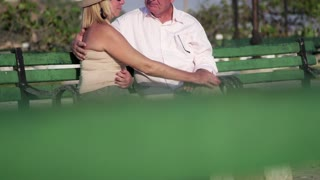 Active retired people with husband and wife relaxing, senior man and woman talking and kissing in city park. Sequence