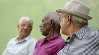 Active retirement and senior people, group of three elderly male friends talking and laughing on bench in public park