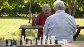 Active retirement, old friends and leisure, two senior men having fun and playing chess game at park. Rack focus from players to chessboard