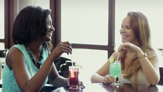 African and latin american female friends drinking cocktails and talking in a pub