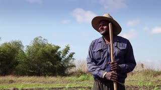 Agriculture and men working in the fields, portrait of black peasant with hat in ANAP cooperative farm in Guines, Cuba, with close up of hands holding shovel. Sequence