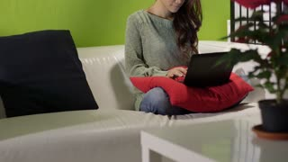 Asian girl with computer on sofa at home