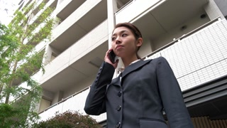 Asian Japanese Happy Woman Talking On Telephone Smartphone Near Skyscraper