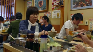 Asian people eating in Tokyo, Japan, Asia. Woman dining in traditional Japanese restaurant. Lifestyle, female friends preparing lunch and cooking Okonomiyaki food. Clients, customers, guests