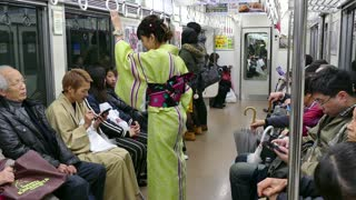 Asian people, tourists, commuters and young couple with traditional Japanese dress traveling on a local train in Kyoto, Japan, Asia. Railway, transport, transportation, travel