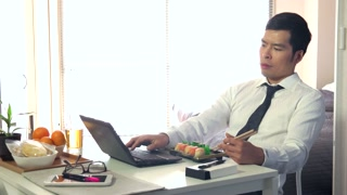 Asian people working at home with pc, young business man at work with laptop computer while having lunch and eating sushi food, businessman talking on mobile phone, busy male manager in living room