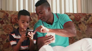 Black Man Teaching Mobile Telephone Technology To Boy At Home