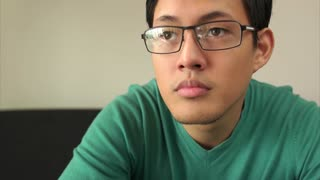 Bored Asian Man Watching TV Changes Channel With Remote
