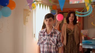 Boy Receiving Present From Girl During Birthday Party At Home