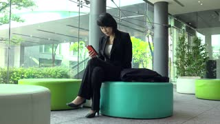 Business travel, people working in hotel lobby, office building. Japanese female manager. Asian businesswoman, girl, woman at work, using mobile phone, telephone, smartphone for email, internet
