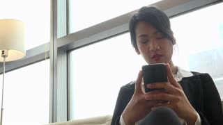 Business travel, people traveling, working in hotel room, Korean female manager. Asian businesswoman, girl, woman at work, texting message with smartphone, mobile phone, telephone for email internet