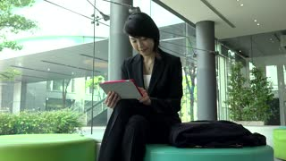Business travel, people working in hotel lobby, office building. Japanese female manager. Asian businesswoman, girl, woman at work, using ipad digital tablet, pc, computer for email, internet