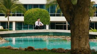 Businessman Meditating Doing Yoga Outside Office Building