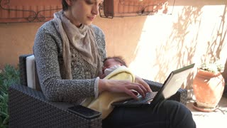 Busy female manager feeding newborn baby. Multitasking mom working, nursing infant. Mother holding child at home, typing on pc, talking on phone. Happy business woman nursing son. Parenting, maternity