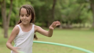 Child and toy, little girl having fun and playing with hula hoop outdoor. Copy space