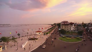 City view of Phnom Penh, Cambodia, with buildings, street, traffic and Tonle Sap river. Time-lapse from sunset to night