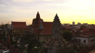 City view of Phnom Penh, Cambodia, with buildings, traffic and Tonle Sap river at sunset