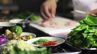 Close-up of cook hands preparing Asian food, chef cooking in restaurant kitchen. Rack focus