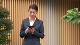 Confident Asian Woman Talking On Mobile Phone Near Office Building